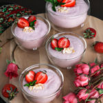 Four bowls of coconut strawberry mousse on a wooden round tray with pink roses and fresh strawberries all around