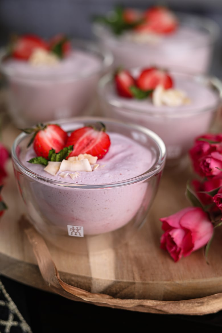 bowls of coconut strawberry mousse on a wooden round tray topped with fresh halved strawberries