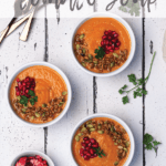 three bowls of tomato soup topped with pomegranate kernels and seeds