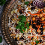 Persian rice in a round tray surrounded by fresh parsley, grilled eggplant and a traditional fabric