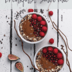 two bowls of chocolate and pumpkin smoothie breakfast topped with raspberries, pomegranate and nuts