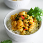 two bowls of coconut shrimp curry on a bed of basmati rice garnished with fresh cilantro leaves
