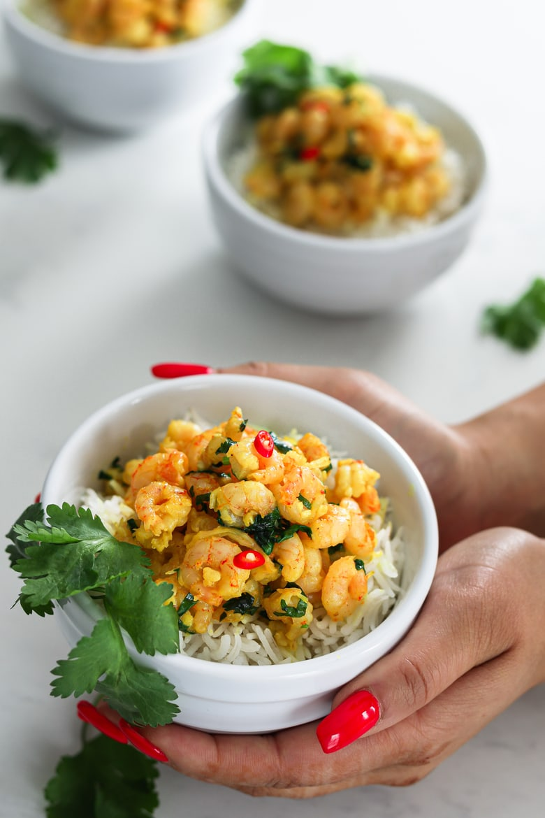 a lady holding a bowl of coconut shrimp curry on a bed of basmati rice garnished with fresh cilantro leaves