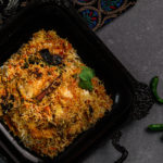 tray of south asian fish biryani with a cinnamon stick on top