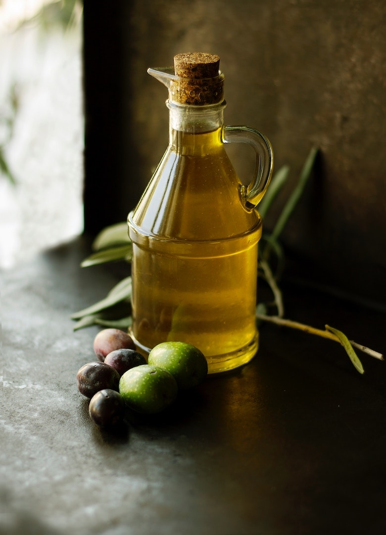 bottle of olive oil with a variety of olives next to it