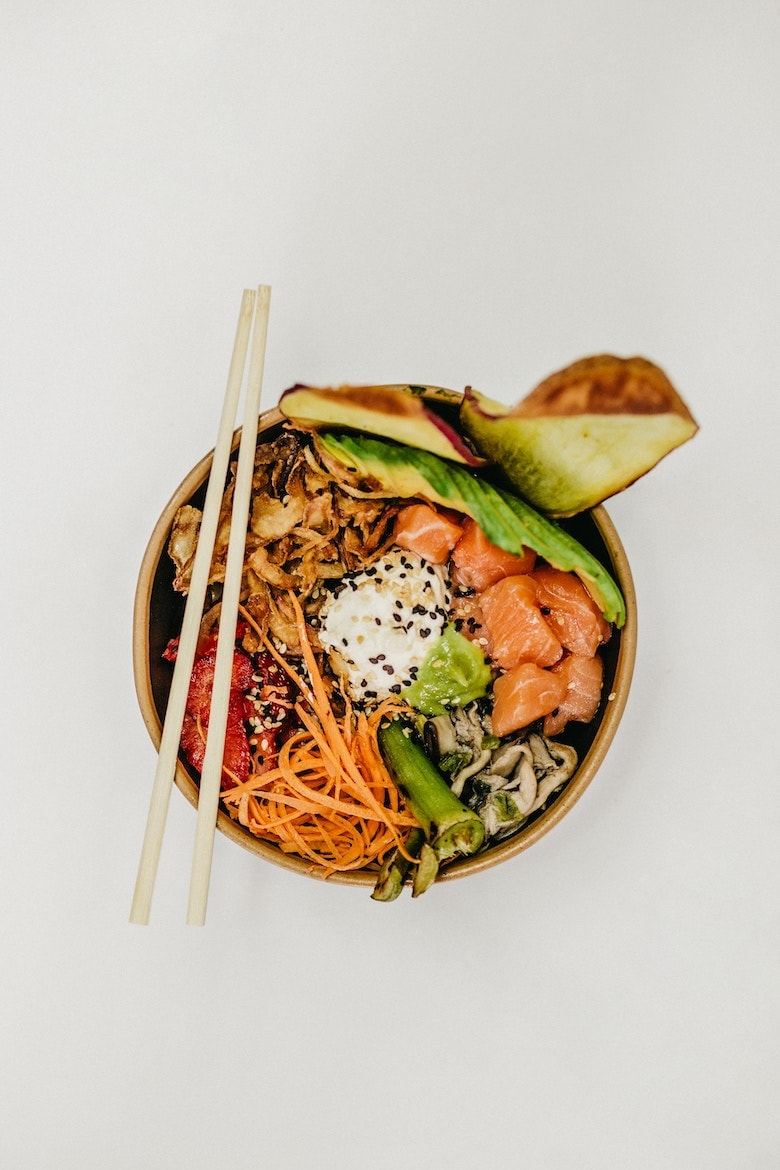 Buddha bowl with salmon and salad with chopsticks resting on top
