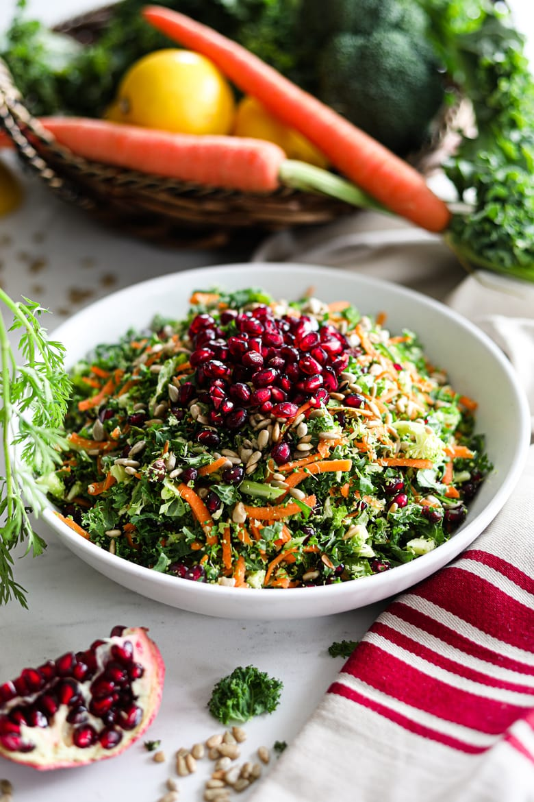 bowl of easy salad recipe with colourful vegetables and topped with pomegranate and seeds surrounded by vegetables