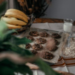 A tray of chocolate oatmeal cookies on a table with a bunch of bananas, rolled oats and a glass of milk