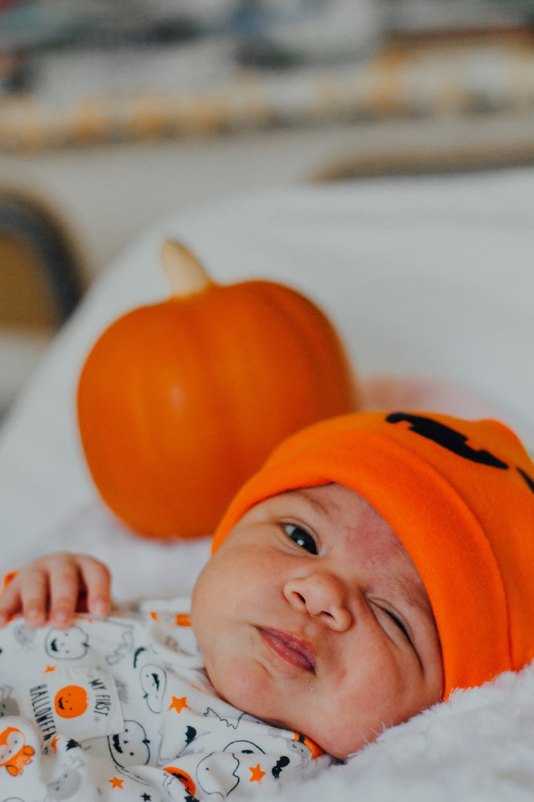 a baby lying on a blanet with an expression wearing a Halloween hat