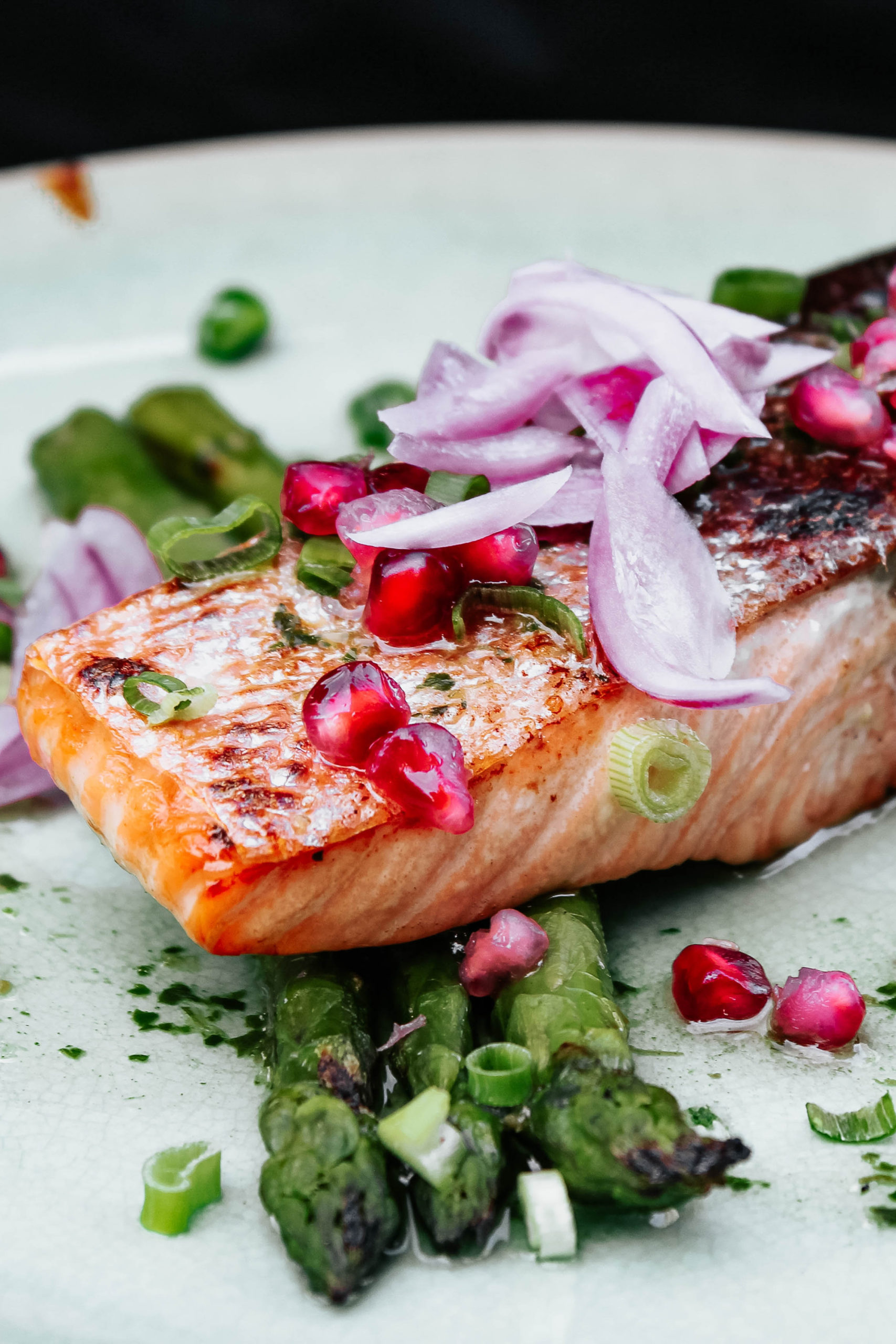 a piece of cooked salmon fillet on a bed of asparagus topped with chopped red onion and pomegranate seeds