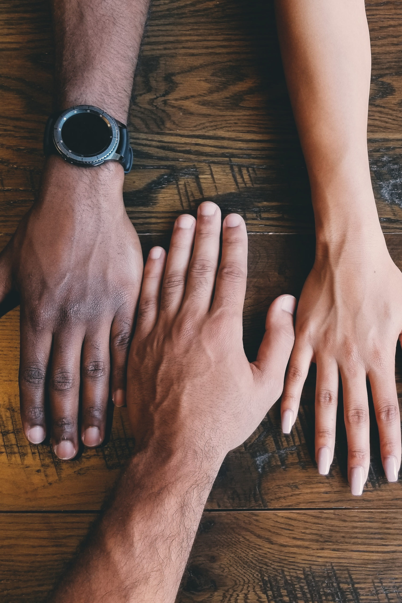 three hands of different people faced down on a wooden table