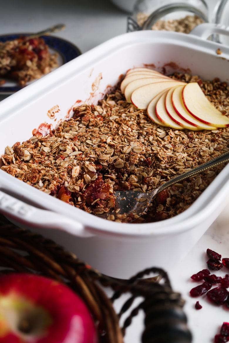 dish with cranberry apple crumble topped with sliced apples with dried cranberries and apple in the foreground