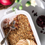 flat-lay image of dish with cranberry apple crumble topped with sliced apples with dried cranberries in a bowl