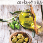 Green olives in olive wood bowl and bottle of olive oil served on old wooden table