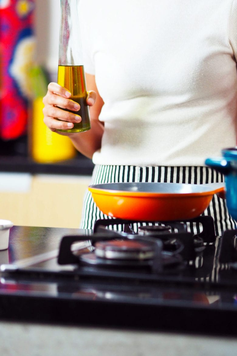 a female standing over a pan on a cook top with a bottle of oil in her hand