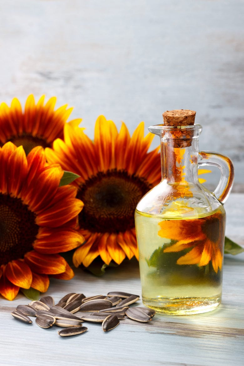 Sunflower Oil with seeds on vintage wooden background