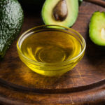 Avocado oil in bowl and fresh avocados on wooden board .
