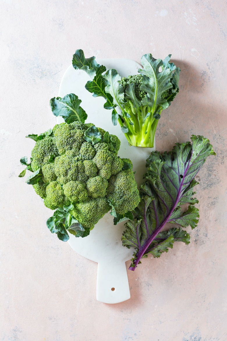 Broccoli and Kale leaves on a marble board. Healthy fresh green vegetables. Top view.