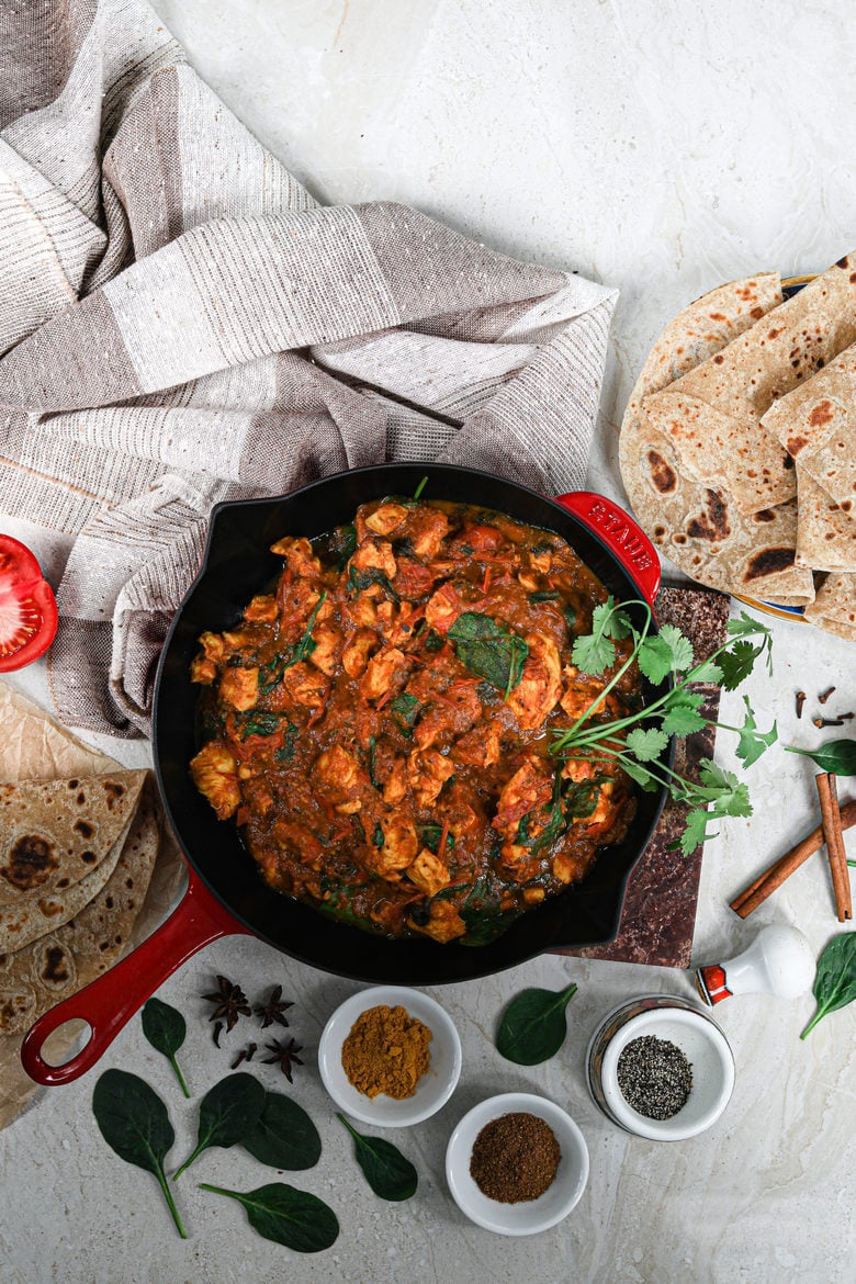 flat lay of a pan of chicken curry made with the best tomato sauce and garnished with fresh herbs with rotis and spices all around