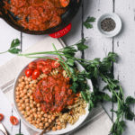 flat lay of a bowl of pasta topped with the best tomato sauce and chickpeas and a herbs decorated on the side