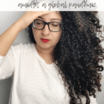 A curly haired woman looking down and expressing anxiety