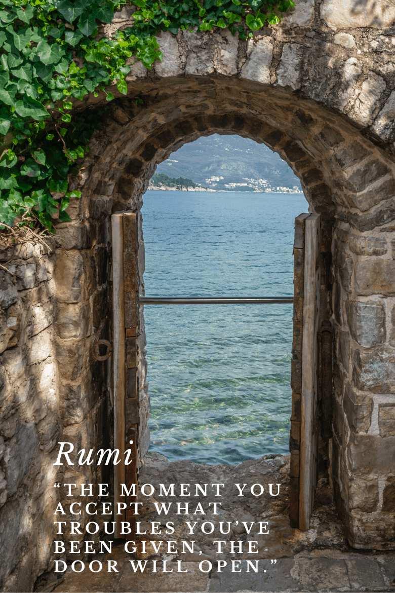 A door opening to the view of the sea with a quote of Rumi