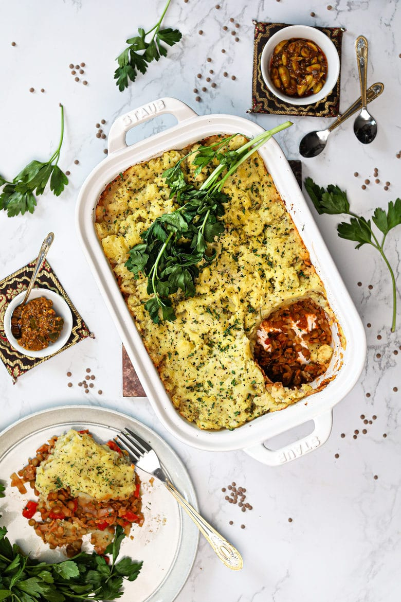 vegan Shepherd's pie in a white baking dish topped with fresh parsley with a portion served in a plate - Ramadan 2021