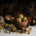 ladoos piled in a coconut shell surrounded by ladoos and pistachios