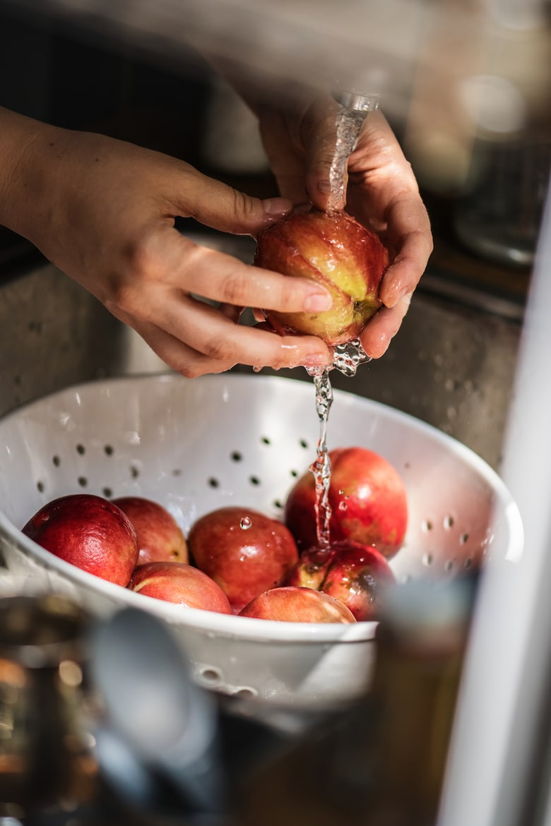 A person washing pomegranate under running water after her grocery trip