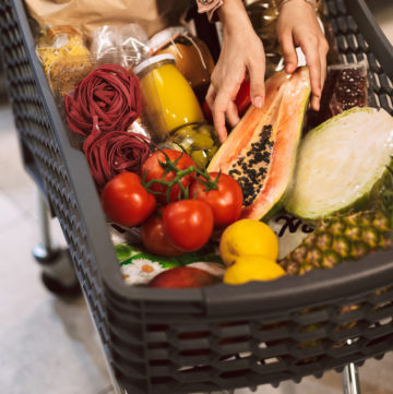 Close up trolley full of fresh products in modern supermarket