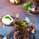 Traditional turkish tea with mint leaves and sweets in a traditional glass on a concrete background