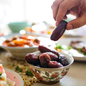 Ramadan healthy eating: Traditional bowl with dried dates being picked up by a hand