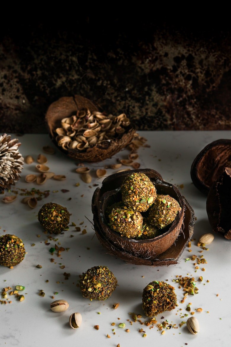 dark and moody image of energy balls piled in a coconut shell