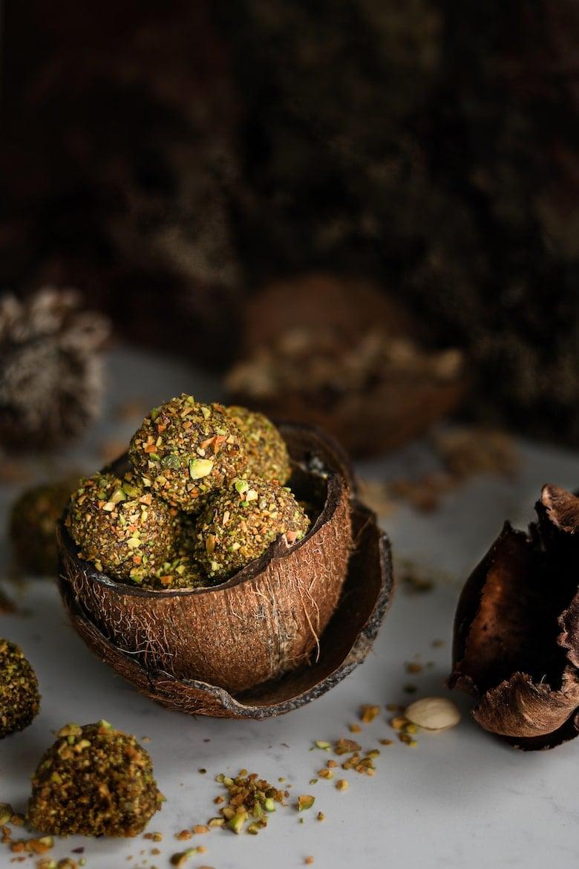 Pistachio ladoos in a coconut shell. Dark and moody shot