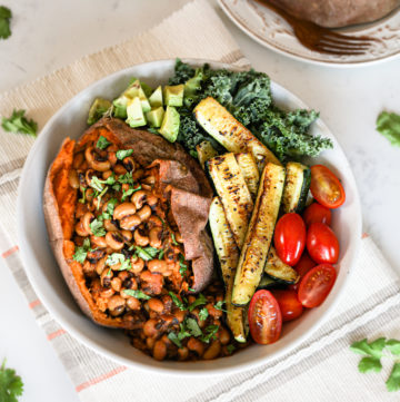 vegan black eyed peas recipe stuffed in a sweet potato with colourful vegetables in a bowl