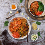 Bowl of vegetable quinoa with garlic shrimp recipe flat-lay
