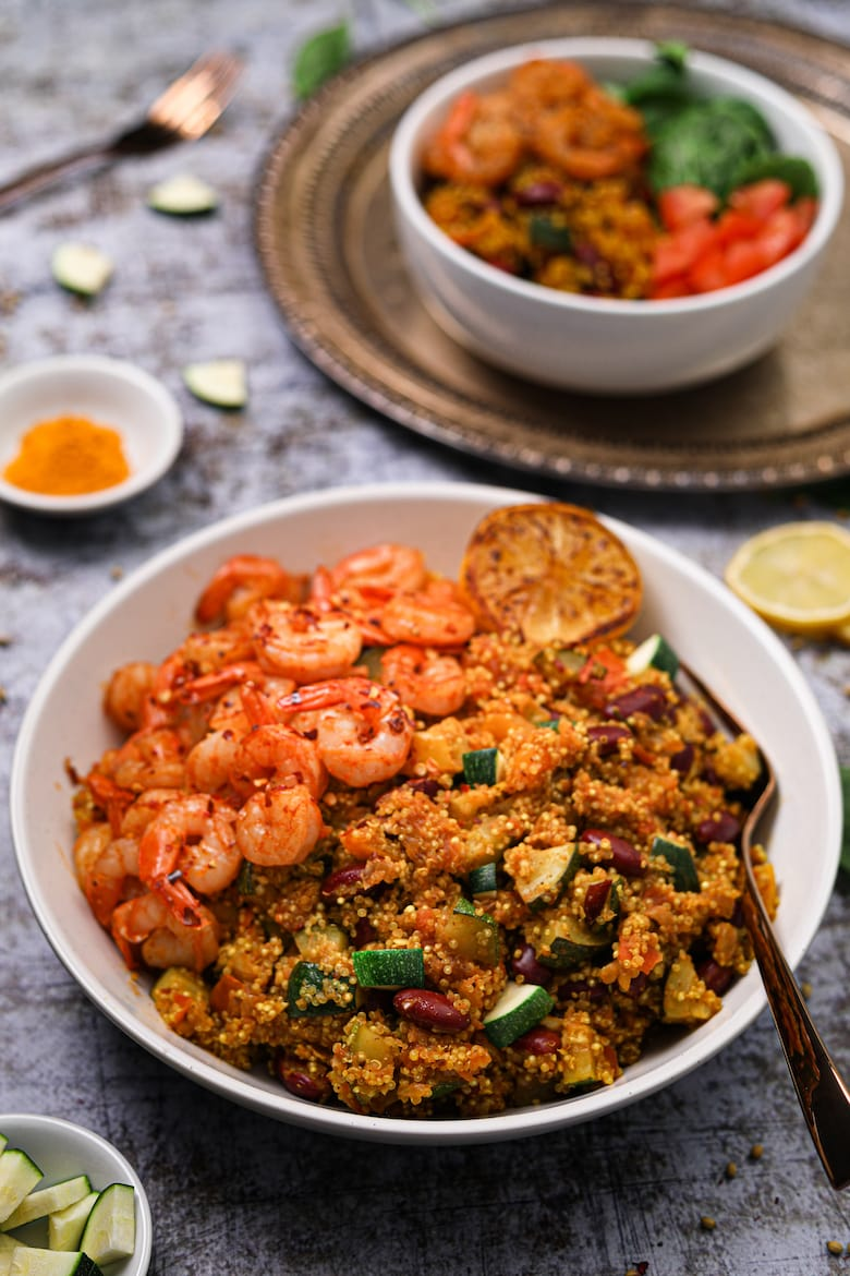 Bowl of vegetable quinoa with garlic shrimp recipe side angle