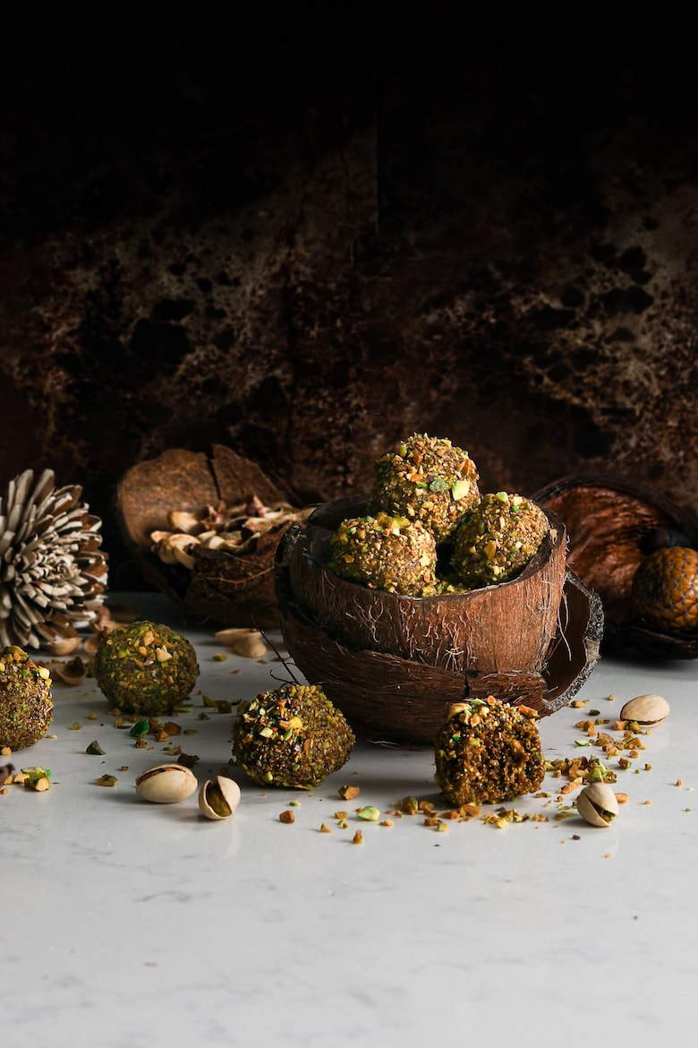 pistachio brown snack energy balls piled in a coconut shell