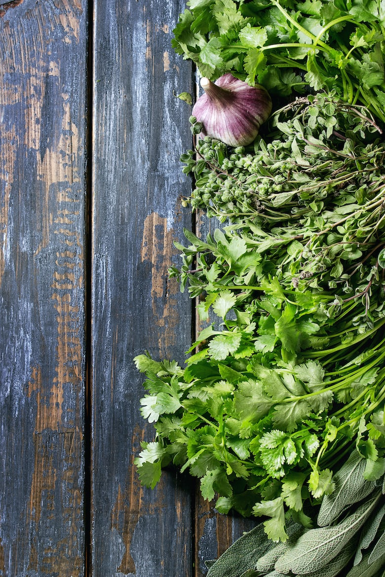 Variety of fresh organic herbs coriander, sage, oregano with garlic over old wooden plank background. Top view with copy space. Food background