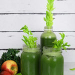 green juice in two mason jars and a bottle with celery stalks inside for decoration, surrounded by apples, kale and lime