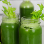green juice in two mason jars and a bottle with celery stalks inside for decoration