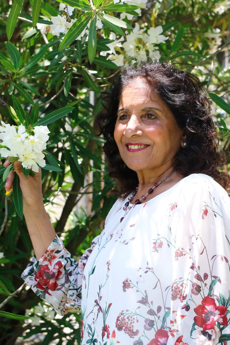 a woman standing next to a tree holding it's flowering branch - outdoors on Mother's Day 2020