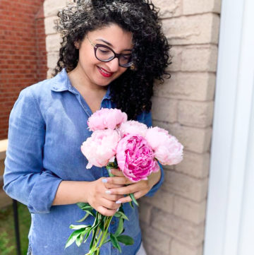 a lady standing with a bunch of pink peonies to celebrate Mother's Day 2020