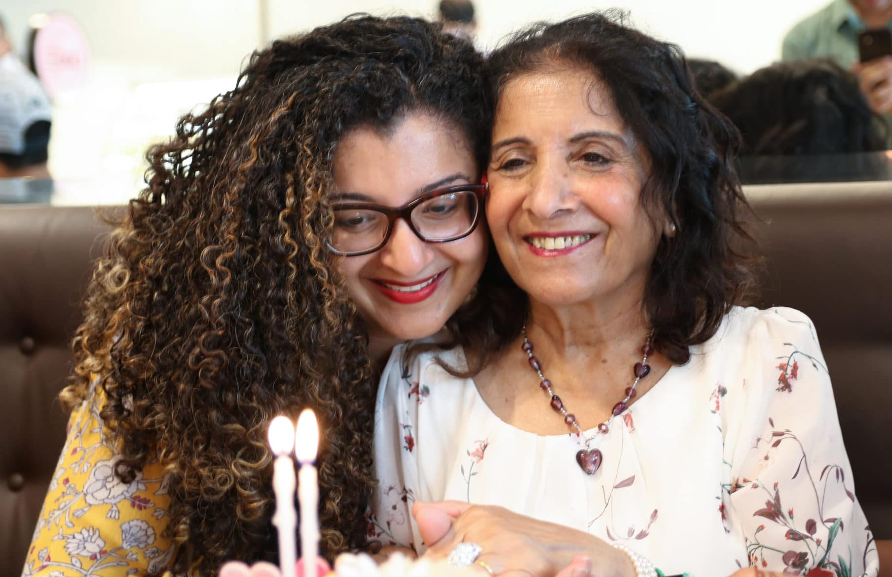 On Mother's Day, a mother and daughter snuggling in front of a cake with 2 candles