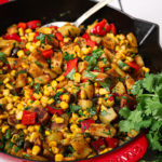 indian chaat salad with corn in a red staub pan with spoon in it
