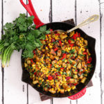 indian chaat salad with corn in a red staub pan with spoon in it and fresh cilantro on the side flat lay