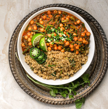 bowl of tikka masala with quinoa and lime and chillies on top in a gold tray - flatlay