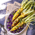 3 corn on the cob on a bed of purple cabbage placed on top of newspapers flatlay