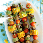 Tray of BBQ vegetable skewers on a bright blue background