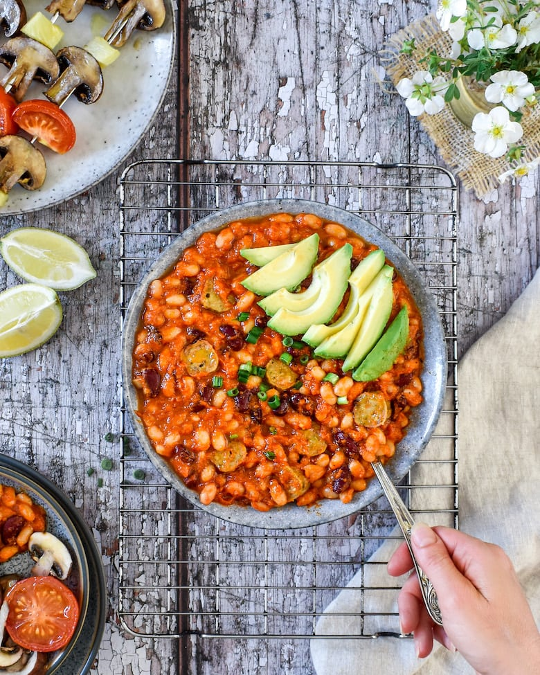 A hand stirring smoky BBQ baked beans topped with avocado slices